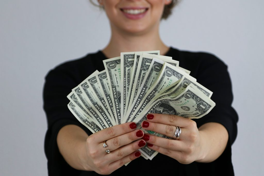 Woman holding a bunch of dollar bills and smiling