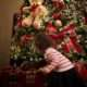 Little girl opening a present in front of a Christmas tree.
