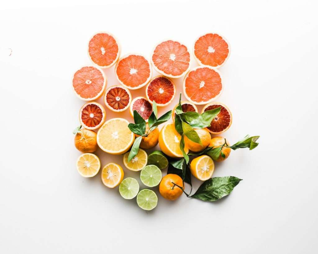 Grapefruits, oranges, lemons and limes on a white background