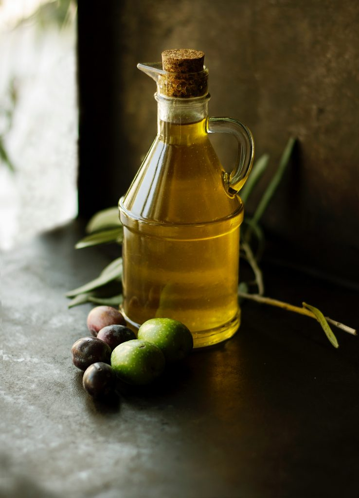 A bottle of French olive oil surrounded by black and green olives