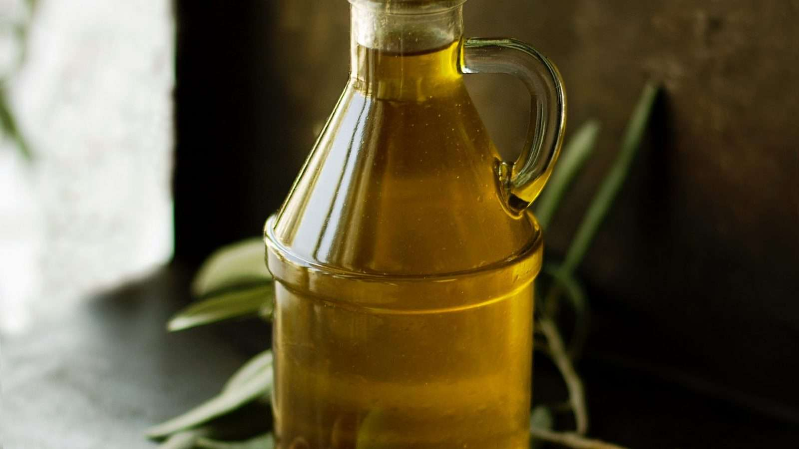 A bottle of French olive oil near black and green olives